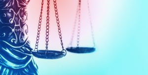 Photo of Justice scales with pink to blue gradient background